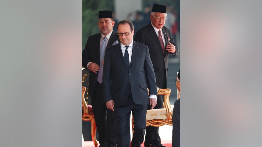 French President Francois Hollande, center, walks ahead of Malaysian King Sultan Muhammad V and Malaysian Prime Minister Najib Razak, right, after inspection of an honor guard during a welcoming ceremony at Parliament House in Kuala Lumpur, Malaysia, Tuesday, March 28, 2017. (AP Photo/Vincent Thian)
