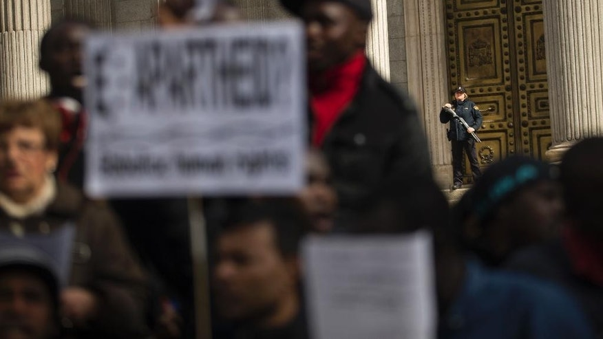A Spanish police officer, right, stands guard outside the Spanish parliament during a protest in Madrid, Tuesday, March 28, 2017.  Few dozens of migrants and locals protested against police harassment and claimed for decriminalizing the sale of copied items on the streets, which is their main source of income. (AP Photo/Francisco Seco)