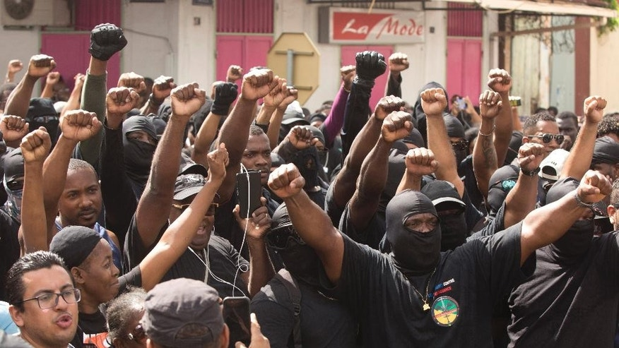 "Masked members of the collective ""500 Brothers"" take part in a march supporting a general strike in Cayenne, French Guiana, Tuesday, March 28, 2017. France announced Tuesday that it will send two high-level ministers to French Guiana as more than 10,000 protesters marched through the streets of the French territory in South America during the second day of a general strike over crime and economic hardship. (AP Photo/Pierre-Olivier Jay)"