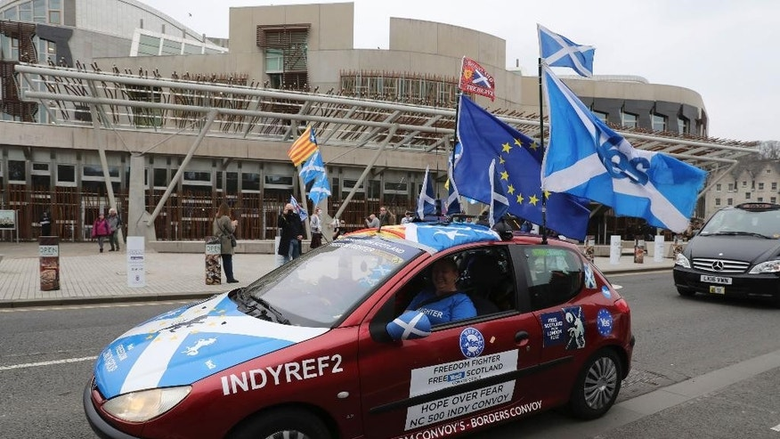 Scottish Independence supporters drive past the Scottish Parliament in Edinburgh ahead of the vote by Members of the Scottish Parliament  to hold a second Scottish independence referendum Tuesday March 28, 2017.  On Monday British Prime Minister Theresa May has met Scotland's leader Nicola Sturgeon for the first time since they faced off in a struggle over a new push for Scottish independence as the U.K. leaves the European Union.   (Andrew Milligan/PA via AP)