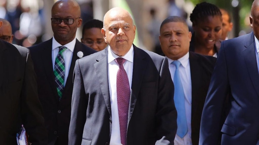 FILE -- In this Wednesday, Feb. 22, 2017 file photo South Africa's finance minister Pravin Gordhan, center, arrives at the South African Parliament to deliver the annual Budget speech in Cape Town, South Africa. Gordhan returned to Johannesburg on Tuesday, March 28, 2017, after being abruptly ordered to pull out of a trade promotion trip to the Britain and the United States, fuelling investor fears that he is about to be fired by President Jacob Zuma. (AP Photo/Schalk van Zuydam, File)