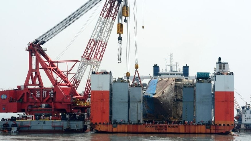 The sunken ferry Sewol is seen on the semi-submersible transport vessel during the salvage operation in waters off Jindo, South Korea, Tuesday, March 28, 2017. South Korean salvage crews on Tuesday found what was presumed to be the remains of one or more of the missing victims of a 2014 ferry disaster that killed 304 people, an official said. (Yonhap via AP)