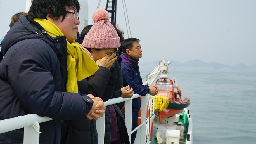 In this photo provided by South Korean ministry of Oceans and Fisheries, relatives of the missing victims wipe tears as they attend religious services in waters off Jindo, South Korea, Tuesday, March 28, 2017. South Korean salvage crews on Tuesday found what is presumed to be the remains of one of the missing victims of a 2014 ferry disaster that killed 304 people, an official said. (South Korean Ministry of Oceans and Fisheries via AP)