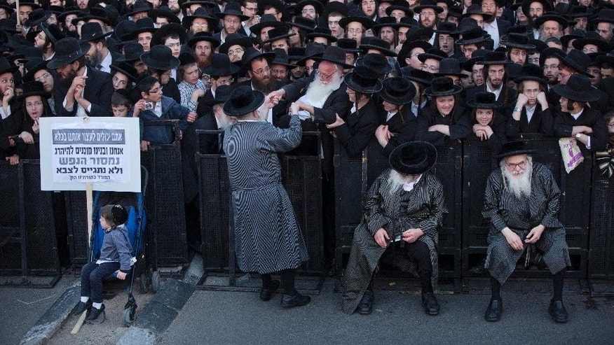 "Ultra-Orthodox Jews take part in a protest against Israeli army conscription in Jerusalem, Tuesday, March 28, 2017. Ultra-Orthodox leaders say they serve the Jewish nation through religious study and prayer and fear integration in the army threatens their insular, pious lifestyle. The sign reads: ""We and our sons are ready to die to preserve our souls and not enlist in the army."" (AP Photo/Oded Balilty)"