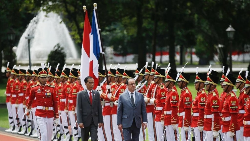 "French President Francois Hollande, right, accompanied by his Indonesian counterpart Joko ""Jokowi"" Widodo, center, inspects an honor guard during a welcome ceremony at Merdeka Palace in Jakarta, Indonesia, Wednesday, March 29, 2017. Hollande is on a two-day visit to the country as part of a regional tour to boost ties with Asia. (AP Photo/Achmad Ibrahim)"