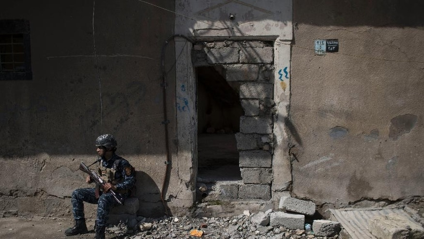 A federal policeman takes a break from inspecting houses during fighting against Islamic State militants on the western side of Mosul, Iraq, Wednesday, March 29, 2017. (AP Photo/Felipe Dana)