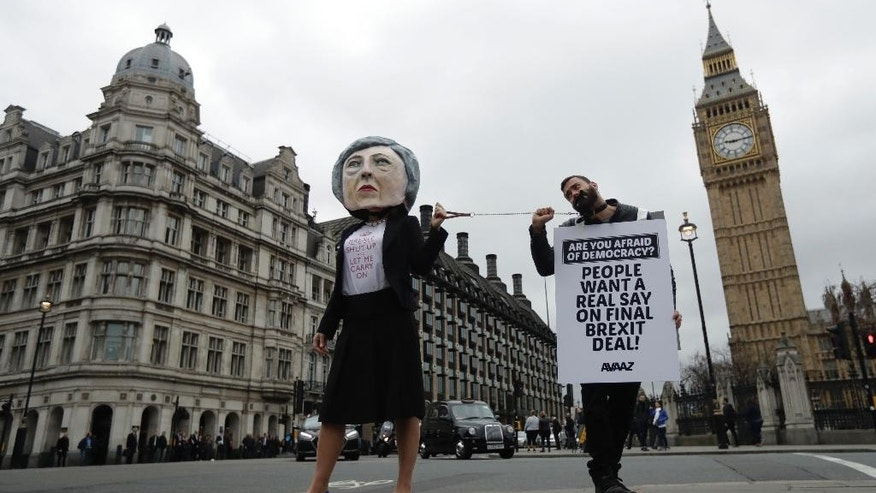 Protesters, one of them with a giant head depicting Theresa May, stand at Parliament Square in central London, Wednesday, March 29, 2017. Britain will begin divorce proceedings from the European Union later on March 29, starting the clock on two years of intense political and economic negotiations that will fundamentally change both the nation and its European neighbors. (AP Photo/Matt Dunham)