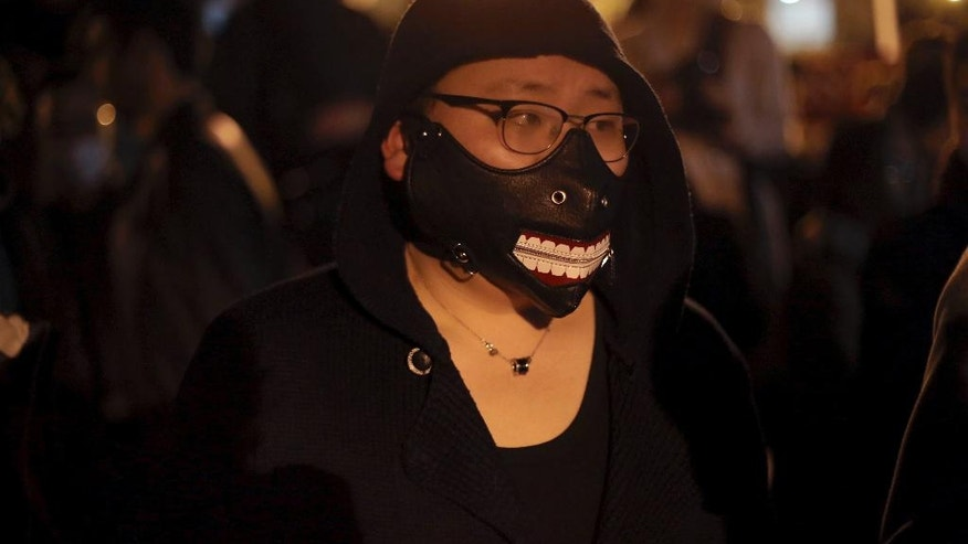 A Chinese immigrant wears a mask during a protest over the fatal shooting of a Chinese man in his apartment, in Paris, Tuesday, March 28, 2017. Chinese immigrants and China's government are protesting a police killing in Paris that prompted violent street clashes and exposed the fears and frustrations of France's large Asian community. (AP Photo/Thibault Camus)