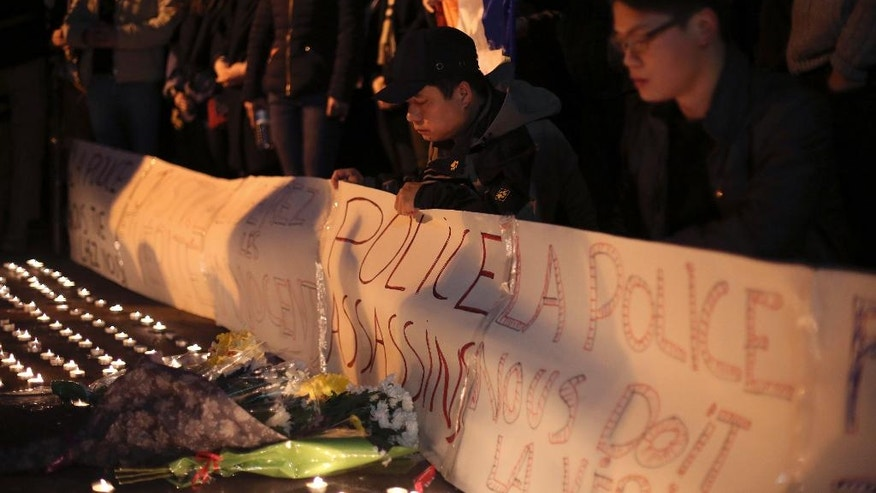 Chinese immigrants pay their respects to a Chinese man killed by the police in his apartment, in Paris, Tuesday, March 28, 2017. Chinese immigrants and China's government are protesting a police killing in Paris that prompted violent street clashes and exposed the fears and frustrations of France's large Asian community. (AP Photo/Thibault Camus)