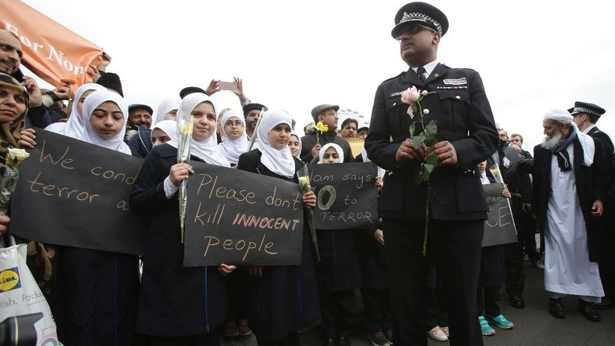 A police officer stands next to muslim girls during a commemorative event to mark last week's attack outside Parliament that killed four people, on Westminster Bridge in London, Wednesday, March 29, 2017. (Yui Mok/PA via AP)