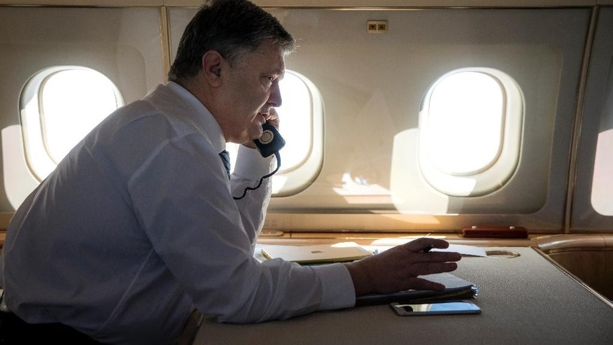 Ukrainian President Petro Poroshenko speaks by phone with Polish President Andrzej Duda from aboard his plane on Wednesday, March 29, 2017. Ukraine's president Poroshenko has condemned an overnight attack on the Polish Consulate in Lutsk, Ukraine, that appeared to involve a shell fired from a grenade launcher. (Mikhail Palinchak, Presidential Press Service Pool Photo via AP)