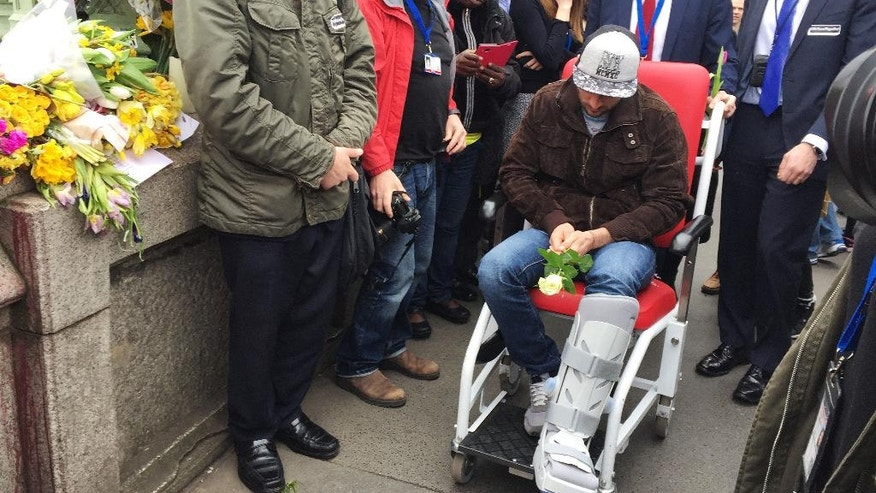 Romanian tourist Andrei Burnaz, who was injured in last week's attack, attends a vigil on Westminster Bridge in London, Wednesday, March 29, 2017. Police officers, Muslim youths and hundreds of others linked hands Wednesday on Westminster Bridge to honor the four people who died in an attack that started on the span a week earlier. The bridge fell silent at 2:40 p.m. to mark the moment when Khalid Masood began mowing down pedestrians, killing three. Masood then fatally stabbed a policeman in a courtyard on the grounds of Parliament (Harriet Line/PA via AP)