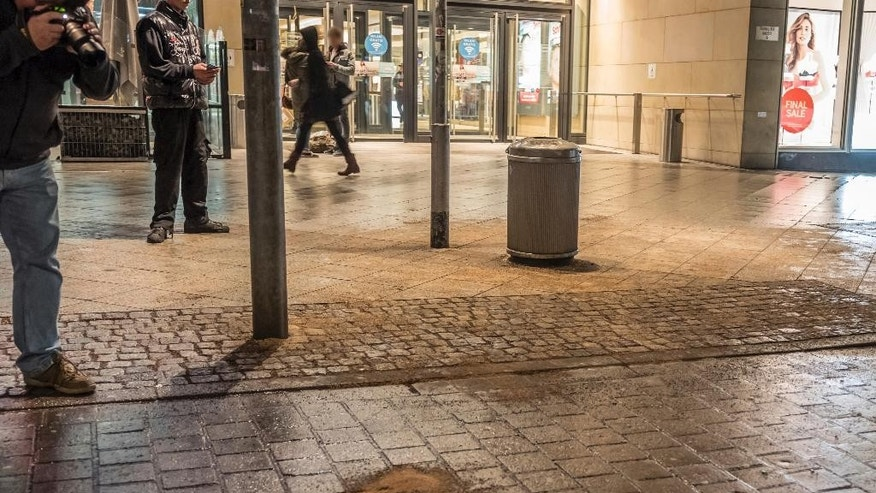 "FILE - In this Feb. 5, 2016 file photo journalists take pictures of the place where Molotov cocktails exploded near a shopping mall in Hannover, Germany. German prosecutors have charged a radicalized 18-year-old man with attempted murder for throwing two Molotov  cocktails into the entrance of a shopping mall in an effort to kill ""infidels."" Prosecutors in Celle identified the German citizen Thursday only as Saleh S., in line with privacy rules. He is the elder brother of a 16-year-old girl, Safia S., who was convicted in January of stabbing and wounding a police officer at the behest of the Islamic State group.  (Uwe Dillenberg/dpa via AP.file)"