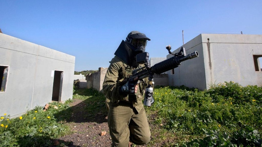 In this Wednesday, March 29, 2017 photo, Israeli soldiers train with paintball guns during a drill at an Army base near Elyakim, Israel. Between myriad concrete buildings with Arabic graffiti that are designed to simulate a typical Lebanese village, dozens of Israeli officers are gearing up for their next battle with Hezbollah guerrillas in the wake of rising tensions between the old adversaries. (AP Photo/Sebastian Scheiner)
