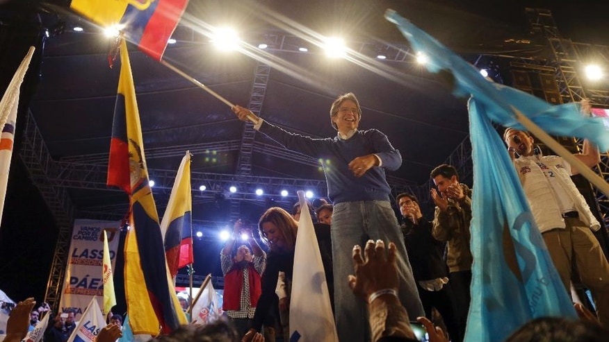 Guillermo Lasso, presidential candidate for the CREO political party holds an Ecuador flag on stage during his closing campaign event ahead of Sunday's presidential runoff election in Quito, Ecuador, Wednesday, March 29, 2017. (AP Photo/Dolores Ochoa)
