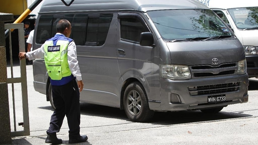 An unidentified van believed to be carrying the body of Kim Jong Nam comes out from the forensic department at Kuala Lumpur Hospital in Kuala Lumpur, Malaysia Thursday, March 30, 2017. Malaysian police on Thursday stopped guarding the morgue that held the body of North Korean leader Kim Jong Un's murdered half-brother, after the van departed amid reports that his remains will leave the country. Shortly after the van left the hospital, police left the building and the morgue was reopened to the public.(AP Photo/Daniel Chan)