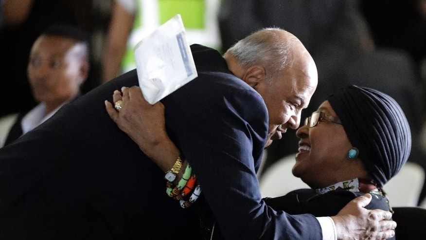 Pravin Gordhan, South Africa's finance minister, left, greets former President Nelson Mandela's wife, Winnie Madikizela-Mandela, during the funeral service for Ahmed Kathrada, at West Park Cemetery in Johannesburg, South Africa, Wednesday, March 29, 2017. Anti-apartheid activist Ahmed Kathrada, who spent 26 years in jail - many of them alongside Nelson Mandela - for working to end South Africa's previous white minority rule, died in Johannesburg on Tuesday morning. He was 87 years old. (AP Photo/Themba Hadebe)