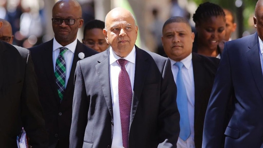 FILE -- In this Wednesday, Feb. 22, 2017 file photo South Africa's finance minister Pravin Gordhan, center, arrives at the South African Parliament to deliver the annual Budget speech in Cape Town, South Africa. President Jacob Zuma's replacement of Gordhan, announced early Friday, March 31, 2017 comes as part of a cabinet shuffle that changes 10 of the country's 35 ministers. Tension had been growing between Zuma and Gordhan, who had a reputation as being resistant to corruption. (AP Photo/Schalk van Zuydam, File)