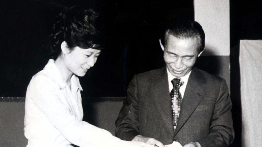 FILE - In this 1977 file photo, former South Korean President Park Chung-hee, right, and his daughter, Park Geun-hye, cast ballots in Seoul, South Korea.  The arrest of South Korea's first female President Park marks a stunning fall for the scion of a powerful general who himself ruled the country during her teenage years and into her 20s. Park Geun-hye was jailed Friday, March 31, 2017,  three weeks after the Constitutional Court stripped her of office over a corruption scandal. Prosecutors accuse her of colluding with a jailed confidante to amass an illicit fortune and allowing the friend to manipulate state affairs.  (Yonhap via AP)