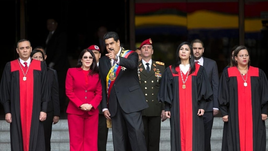 FILE - In this Jan. 15, 2017 file photo, Venezuela's President Nicolas Maduro speaks with first lady Cilia Flores as they arrive to the Supreme Court, before delivering his state of the union address, in Caracas, Venezuela.  Venezuela's Supreme Court ruled Wednesday night, that it can take over responsibilities assigned to Congress. Maduro opponents are saying it's part of an attempt to install a dictatorship in the South American nation. Justices pictured from left to right; Supreme Court Vice President Maikel Moreno; Supreme Court President Gladys Gutierrez; and Supreme Court Justice Indira Alfonso. (AP Photo/Ariana Cubillos, File)
