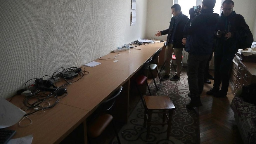 Journalists examine empty tables after Belarusian police conducted a search and confiscated equipment in the office in capital Minsk, Belarus, on Friday, March 31, 2017. The Belsat channel, which is part of Polish public broadcaster TVP, and is aimed at providing an alternative to Belarus' state-controlled television, reported amid the Friday raids that police were seizing equipment at two of its offices in Minsk. (AP Photo/Sergei Grits)