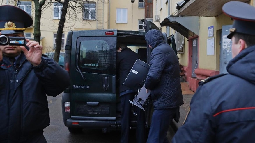 Belarusian Interior Ministry officer films nearby journalists as another carries confiscated equipment to police bus near the office of Belsat channel as they conduct a search in the office in capital Minsk, Belarus, on Friday, March 31, 2017.  The Belsat channel, which is part of Polish public broadcaster TVP, and is aimed at providing an alternative to Belarus' state-controlled television, reported amid the Friday raids that police were seizing equipment at two of its offices in Minsk. (AP Photo/Sergei Grits)