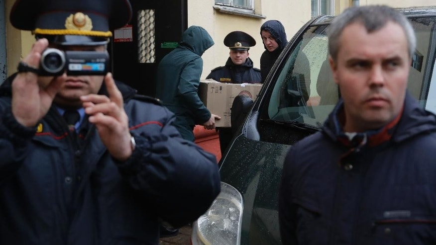 Belarusian Interior Ministry officer films nearby journalists, near the office of Belsat channel as they conduct a search in the office in capital Minsk, Belarus, on Friday, March 31, 2017.  The Belsat channel, which is part of Polish public broadcaster TVP, and is aimed at providing an alternative to Belarus' state-controlled television, reported amid the Friday raids that police were seizing equipment at two of its offices in Minsk. (AP Photo/Sergei Grits)