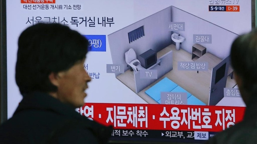 "People watch a TV screen showing an image of solitary cell of Seoul Detention Center used by former South Korean President Park Geun-hye during a news program at the Seoul Railway Station in Seoul, South Korea, Friday, March 31, 2017. For a person whose life always seemed to revolve around South Korea's huge presidential palace, the next several months are likely to be lived on a much smaller scale. Park entered the Seoul Detention Center in a black sedan before dawn Friday after a court approved her arrest on corruption allegations. The letters read: ""Solitary cell of Seoul Detention Center"". (AP Photo/Ahn Young-joon)."