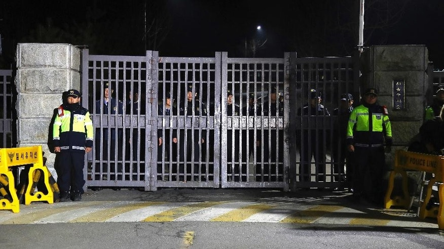 Police officers stand guard in front of Seoul Detention Center in Uiwang, South Korea, Friday, March 31, 2017. For a person whose life always seemed to revolve around South Korea's huge presidential palace, the next several months will be lived on a much smaller scale. Ousted South Korean President Park Geun-hye entered the Seoul Detention Center in a black sedan before dawn Friday after a court approved her arrest on corruption allegations. (Hwang Gwang-mo/Yonhap via AP)