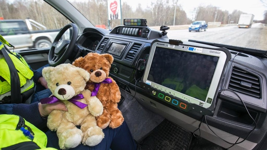 In this undated image released by Estonian charity Traumamommik  on Friday March 31, 2017, shows an Estonian police officer holding teddy bears for traumatized children. An Estonian charity plans to donate two teddy bears to every police car in the Baltic country in case officers need to comfort traumatized children. ( Dmitri Kotjuh/Traumamommik via AP)