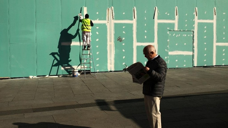 A worker applies sealing putty on a construction fence placed around a shop to be restored at the Sol square in Madrid, Wednesday, March 29, 2017.  The square, one of the most visited places of the Spanish capital, is a lively commercial area full of shops, restaurants and pubs. (AP Photo/Francisco Seco)