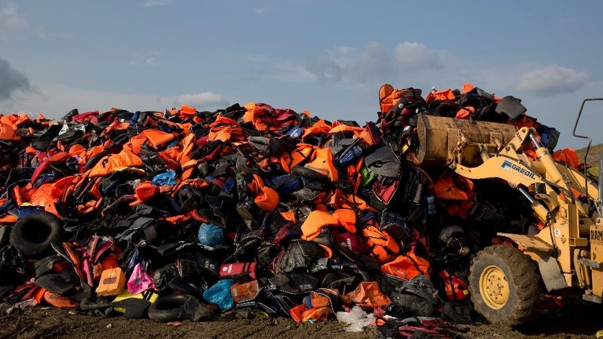 FILE - In this Thursday, Sept. 24, 2015 file photo, an excavator works on a huge pile of life vests and dinghies that have been used by migrants at a local dump of the island of Lesbos, Greece. (AP Photo/Petros Giannakouris, File)