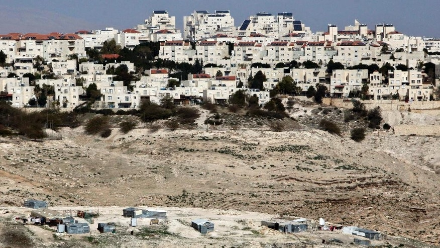 FILE -- In this Sunday, Jan. 22, 2017 file photo, the Israeli settlement of Maaleh Adumim looms over Arab Bedouin shacks in the West Bank. Prime Minister Benjamin Netanyahu has ordered a slowdown of construction in territory Palestinians want for a state in a gesture to President Donald Trump at the same cabinet meeting where he approved the first new settlement in two decades the heart of the West Bank. Netanyahu's government is dominated by pro-settler hard-liners who oppose Palestinian statehood on either security or religious grounds. (AP Photo/Mahmoud Illean, File)