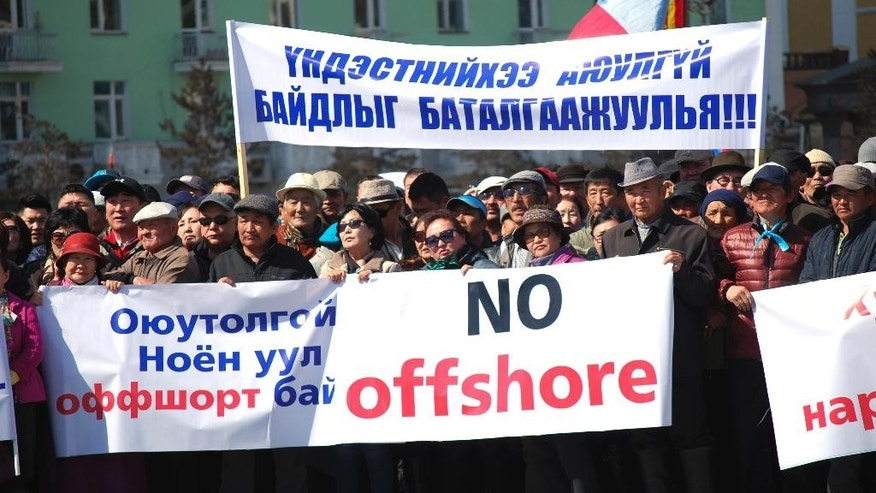 "Mongolians hold up banners which read: ""Oyu-Tolgoi mine and the Noyon Mountain are in offshore account."" and ""Let's guarantee security of our nation"" during a protest in Ulaanbaatar, Mongolia, Friday, March 31, 2017. Hundreds of Mongolians have protested in the capital Ulaanbaatar over the alleged theft of government funds deposited in offshore accounts. (AP Photo/Ganbat Namjilsangarav)"