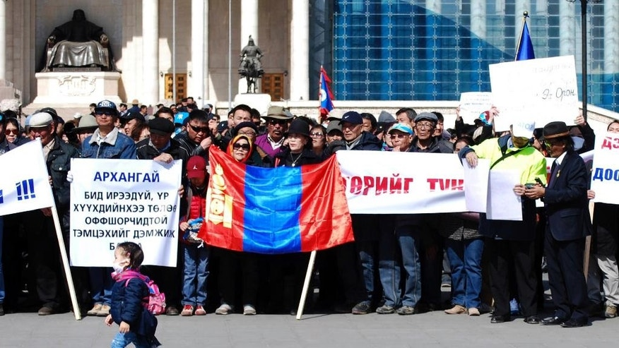 "A child walks past Mongolians holding up banners, one of which reads ""Arkhangai - We support fight against offshore account holders for the sake of our future, children"" during a protest in Ulaanbaatar, Mongolia, Friday, March 31, 2017. Hundreds of Mongolians have protested in the capital Ulaanbaatar over the alleged theft of government funds deposited in offshore accounts. (AP Photo/Ganbat Namjilsangarav)"