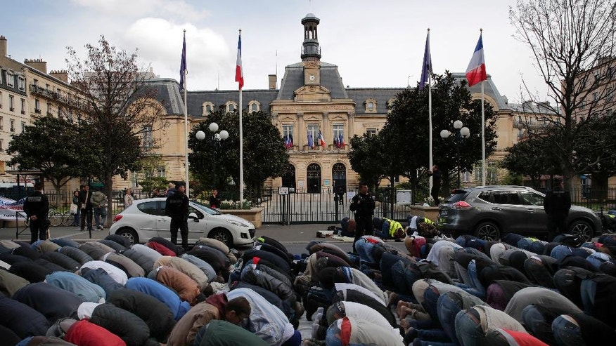Hundreds of Muslims pray on the street in front of the town hall plaza, seen behind, in the Paris suburb of Clichy la Garenne, Friday, March 31, 2017. They protest the closure of a prayer room and call attention to their wishes for a mosque in their town, with a large Muslim population. (AP Photo/Christophe Ena)