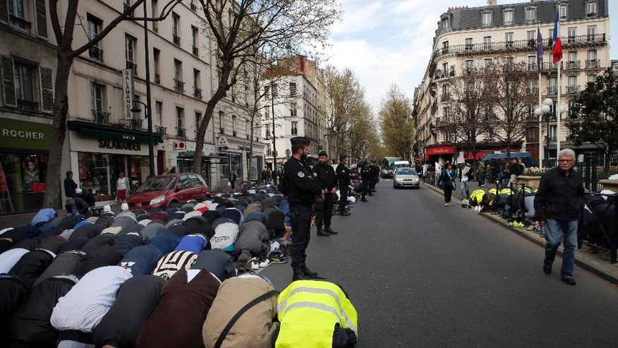 Hundreds of Muslims pray on the street in front of the town hall plaza in the Paris suburb of Clichy la Garenne, Friday, March 31, 2017. They protest the closure of a prayer room and call attention to their wishes for a mosque in their town, with a large Muslim population. (AP Photo/Christophe Ena)