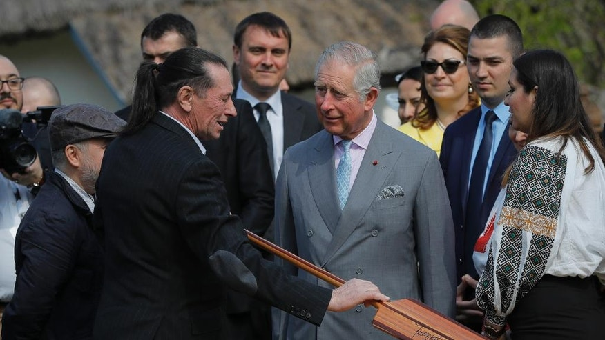 Britain's Prince Charles, center, speaks to Ivan Patzaichin, former Romanian rowing star and four times Olympic medalist, in Bucharest, Romania, Thursday, March 30, 2017. Britain's Prince Charles toured the Village Museum during his visit to Romania, Italy and Austria, a trip seen as an effort to reassure European Union nations that Britain remains a close ally. (AP Photo/Vadim Ghirda)