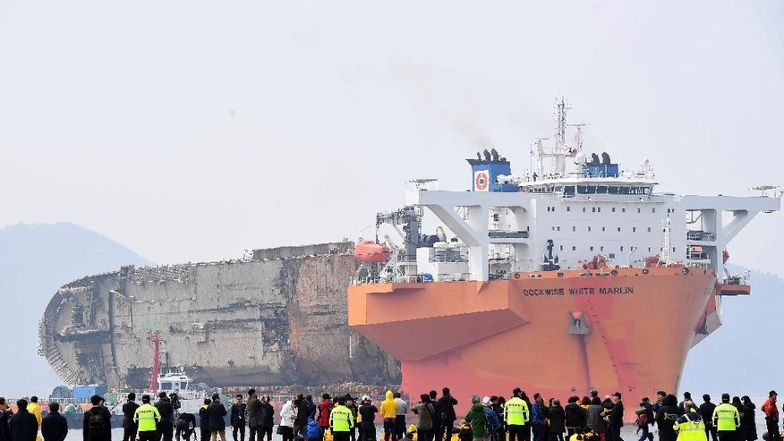The sunken ferry Sewol sitting on a semi-submersible transport vessel arrive at a port in Mokpo, South Korea. Friday, March 31, 2017. The corroding 6,800-ton ferry raised from the bottom of the sea last week arrived at a South Korean port Friday, where it will be searched for the remains of nine missing passengers from a 2014 sinking. (Yonhap via AP) KOREA OUT