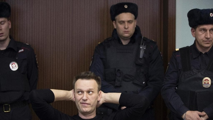 Russian opposition leader Alexei Navalny, foreground left, waits to hear a sentence in court in Moscow, Russia, Thursday, March 30, 2017. Many Western countries have condemned the arrests and called for the release of those sentenced to jail, including opposition leader Alexei Navalny, Putin's most prominent foe. (AP Photo/Pavel Golovkin)