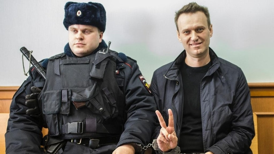 Russian opposition leader Alexei Navalny, right, shows a V-sign for the media in court in Moscow, Russia, Thursday, March 30, 2017 Russian President Vladimir Putin has rejected Western calls for the release of jailed protesters, including opposition leader Alexei Navalny, in his first public comments about a wave of nationwide rallies against government corruption. (AP Photo/Evgeny Feldman)