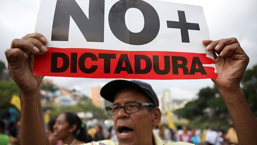 "An opposition supporter holding a placard that reads ""No more dictatorship"" in Caracas, Venezuela March 31, 2017."