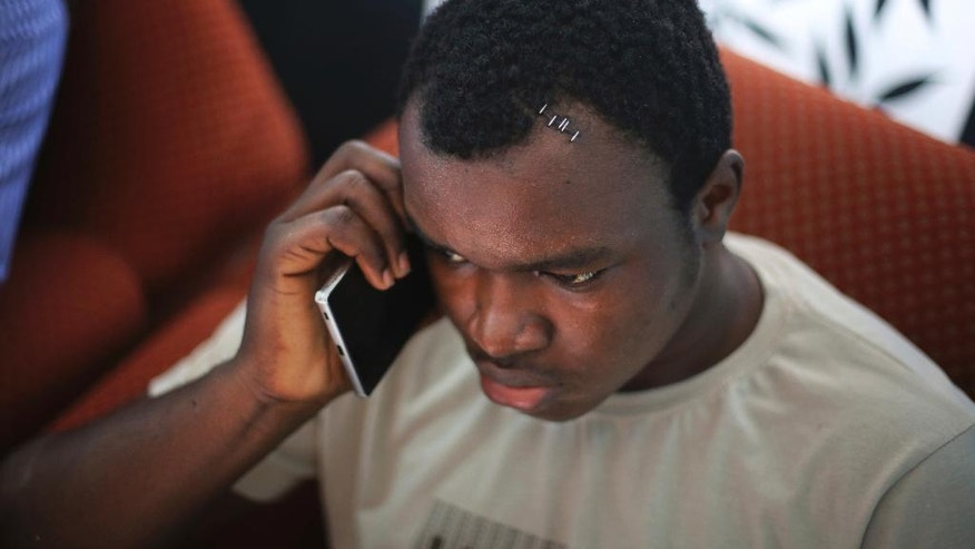 In this Friday, March 31, 2017 photo, Nigerian student Endurance Amalawa, 21, speaks to his parents on a mobile phone inside his apartment in Greater Noida, India. Endurance's body was dotted with medical staples, on his temple, his cheek and both arms, after dozens of screaming men attacked him with bricks, sticks and belts. The violence started March 24 when a teenage boy disappeared in Greater Noida, outside New Delhi, and angry relatives claimed he'd been killed by his Nigerian neighbors. A mob of people began searching the area for Africans, with some accusing kidnappers of eating the boy. (AP Photo/Altaf Qadri)