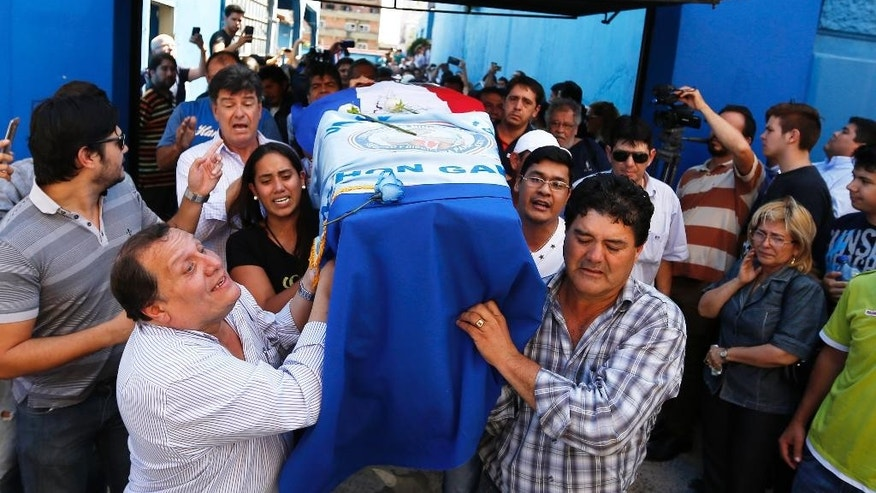 Relatives carry a coffin with the remains of Rodrigo Quintana, a member of the Authentic Radical Liberal Party, who was killed in an incident at party's headquarters away from congress at the party's headquarters on Friday, in Asuncion, Paraguay, Saturday, April 1, 2017. Clashes erupt between police and protesters outside Paraguay's congress, with demonstrators setting fires around the building after a majority of senators carry out what some was called an irregular vote to allow presidential re-election. (AP Photo/Jorge Saenz)