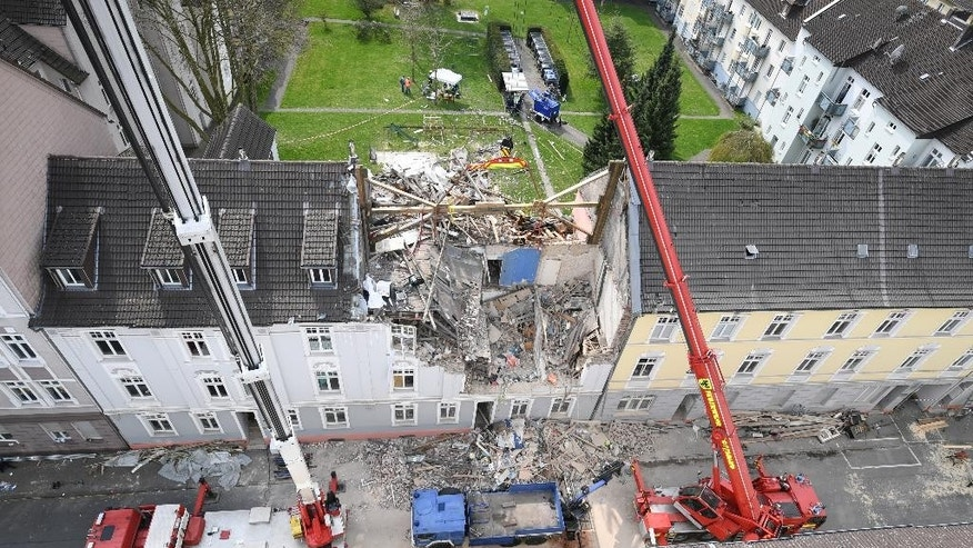 Cranes stand in front of an apartment building which was destroyed in an explosion on the previous day in Dortmund, Germany, Saturday, April 1, 2017. One person died in the explosion in the building. Rescue forces found the body of a female resident on Saturday morning. ( Bernd Thissen/dpa via AP)