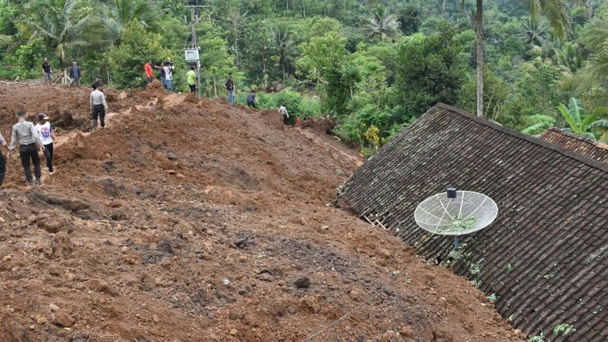 Rescuers search for victims in a neighborhood hit by a landslide in the village of Banaran, Ponorogo, East Java, Indonesia, Saturday, April 1, 2017. More than two dozen people were reported missing on Saturday after the rain-triggered landslide struck a village on Indonesia's main island of Java. (AP Photo/Firdaus)