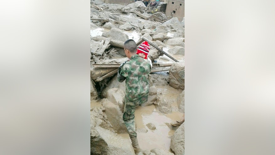 In this handout photo released by the Colombian National Army, a soldier carries a child in Mocoa, Colombia, Saturday, April 1, 2017, after an avalanche of water from an overflowing river swept through the city as people slept. The incident triggered by intense rains left at least 100 people dead in Mocoa, located near Colombia's border with Ecuador. (Colombian Army Photo via AP)