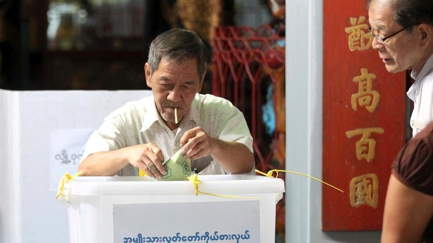 A voter casts his ballot at a polling station in Yangon, Myanmar, Saturday, April 1, 2017. Voting is underway in 19 by-elections in Myanmar, in the first test of the popularity of Aung San Suu Kyi's National League for Democracy since it formed the government a year ago. (AP Photo/Thein Zaw)