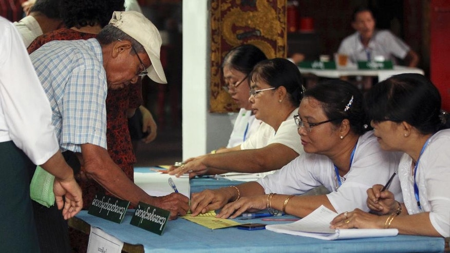 A voter signs his name to get a ballot sheet from an official of the Union Election Commission at a polling station in Yangon, Myanmar, Saturday, April 1, 2017. Voting is underway in 19 by-elections in Myanmar, in the first test of the popularity of Aung San Suu Kyi's National League for Democracy since it formed the government a year ago. (AP Photo/Thein Zaw)