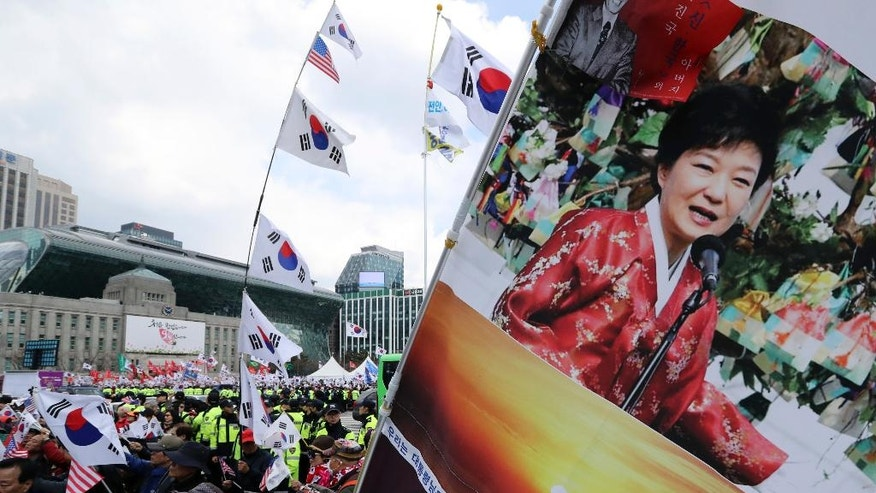 Supporters of former President Park Geun-hye hold a banner with pictures of Park and national flags before a rally at downtown Seoul, South Korea, Saturday, April 1, 2017. Thousands of supporters of arrested former President Park gather in South Korea's capital on Saturday to call for her release. (AP Photo/Lee Jin-man)